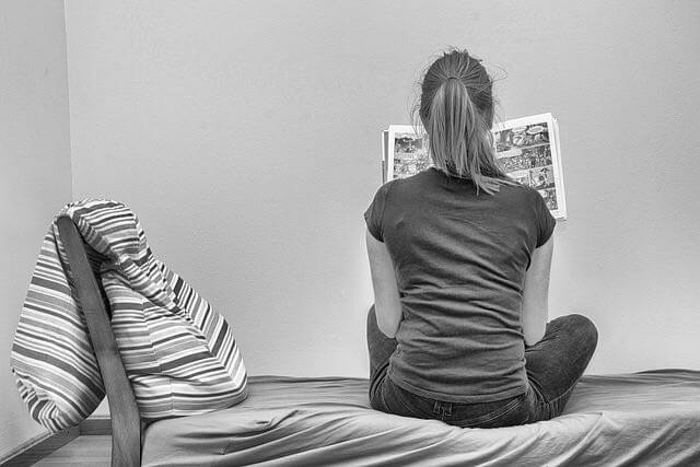 A girl on bed holding a book in her hands & read it