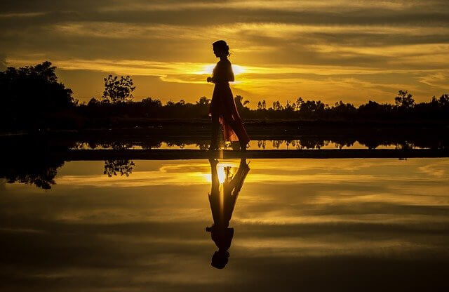 Valentine Day for Singles - How to Make Valentine Day Special - A girl is walking across river & her shadow is visible in the water. The time seems evening or morning as it's yellowish all around